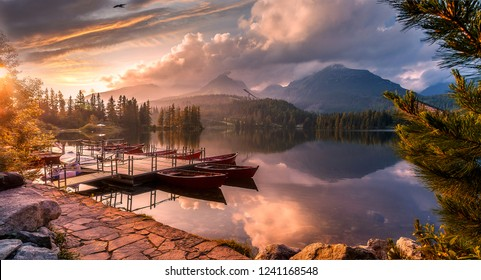 Magical Nature Landscape with Dramatic Sky in Mountain Valley. Majestic  lake Strbske Pleso during Sunset. Overcast sky reflected in calm water. Wooden boats on Foreground. Amazing natural Scenery