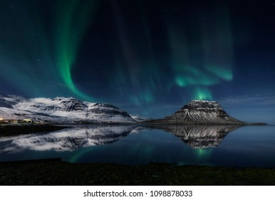 Magical northern lights appearing behind the Icelandic mountains of Kirkjufell