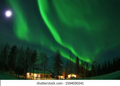 The magical Northern Lights and Moon shine over the houses in Finnish Lapland Levi