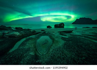 Magical Northern Lights and mountains on a beach in the Lofoten Islands, Northern Norway.