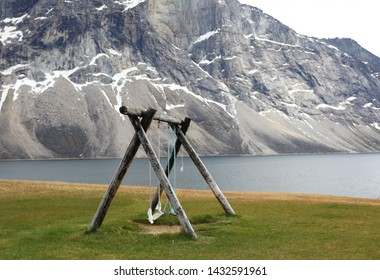 Magical old wooden swing hanging on pillar, landscape colony Greenland, Nuuk fjord
