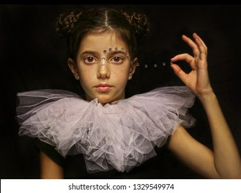 Magical portrait of a  girl wearing a lace collar holding beads