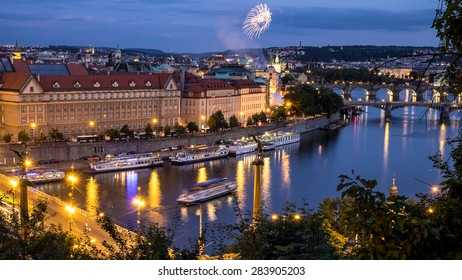 Magical Prague with fireworks along Vltava river at dusk.