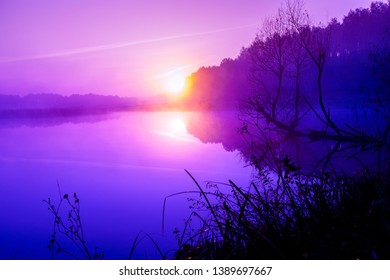 Magical purple sunrise over lake. Misty morning, rural landscape, wilderness