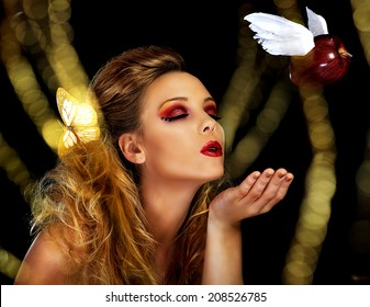 A magical scene where a beautiful blonde model blows a kiss, represented by a red apple with wings, through a field of gold.