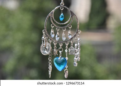 A magical spell. Silver amulet with gems and pendants. Believing in magic protecting the holder of amulet. Jewelry charm or talisman. Name amulet for good luck. Luck amulet hung out outdoor.