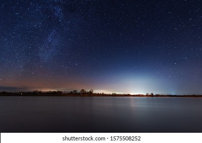 A magical starry night on the river bank with a milky way in the sky and falling stars in the winter.