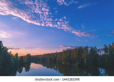 Magical sunrise over lake with beautiful reflection on water. Rural landscape
