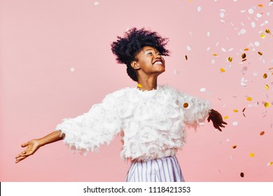 A magical time - Portrait of a very happy girl with arms out, smiling at confetti falling