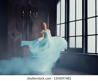 The magical transformation of Cinderella into a beautiful princess in a luxurious dress. Young women are blonde, spinning and dancing in a dark, gloomy room, the dress fluttering on the fly. Art photo