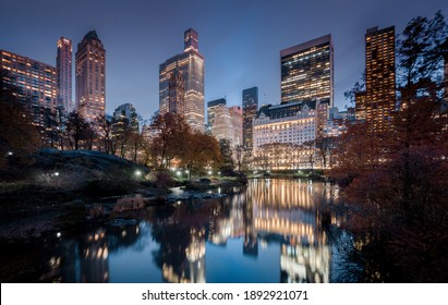 Magical twilight panorama view of New York City Midtown skyline reflecting in the Pond at Central Park South seen from Gapstow Bridge during blue hour at dusk, New York, USA - Shutterstock ID 1892921071