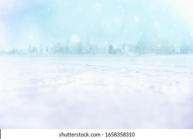 MAGICAL WINTER LANDSCAPE WITH SNOW FLAKES FALLING ON ICE FIELD AND FOREST ON BACKGROUND