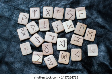 Magical wooden runes on the black genuine leather