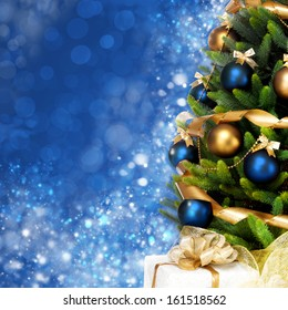 Magically decorated Christmas Tree with balls, ribbons and garlands on a blurred blue shiny, fairy and sparkling background