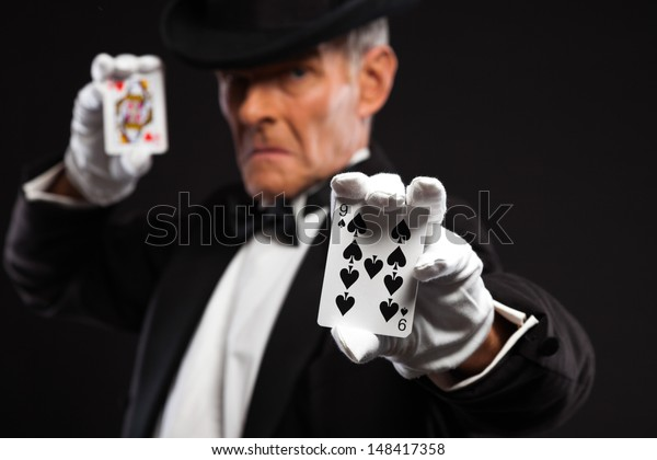 Magician with black suit and hat holding set of cards. Studio shot against black.