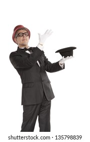 A magician in a black suit holding an empty top hat isolated on white background