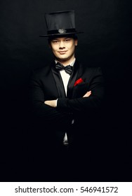 A magician in a black suit holding an empty top hat and magic wand isolated on black background