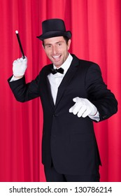 A Magician In A Black Suit Holding Magic Wand