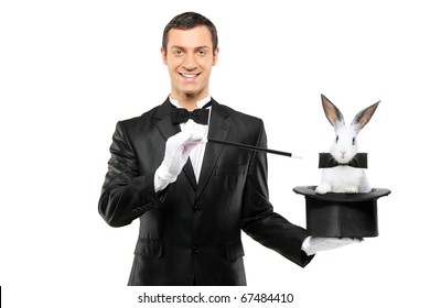 A magician in a black suit holding a top hat with a rabbit in it isolated on white background