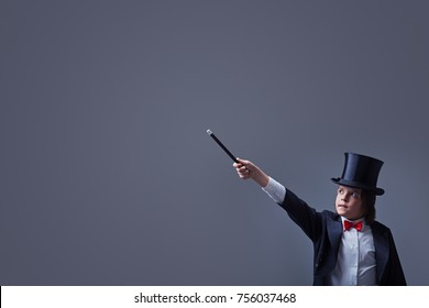 Magician boy with hardhat and elegant tuxedo pointing to copy space with magic wand
