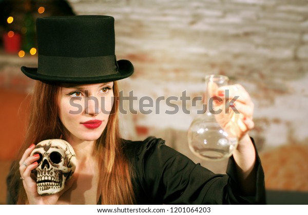 Magician girl holding a skull and test tube