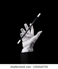 magician hand and wand floating in the air, high contrast image, isolated on black