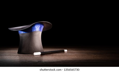 magician hat and wand on a wooden background, high contrast image