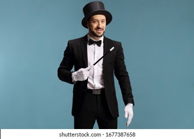 Magician holding a magic wand isolated on blue background
