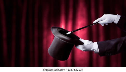 magician holding a top hat and magic wand with a red curtain as background