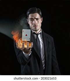 Magician holds flaming card in his hands