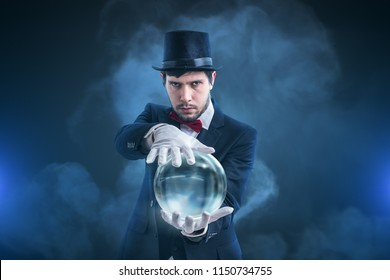 Magician or illusionist is fortune telling and predicting future from magical crystal ball.