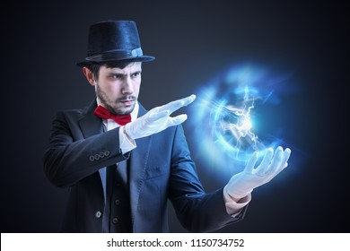 Magician or illusionist is showing bright plasma ball radiating light rays.