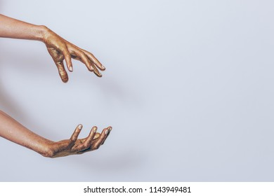 Magician make summon gesture imitation on plain gray background with copy space. Woman's hands painted golden glitters doing illusionist performance.