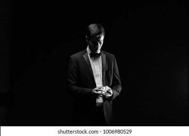 Magician with playing cards,Suprised magician,Juddler man,Mystery person.Black magic,Illusion