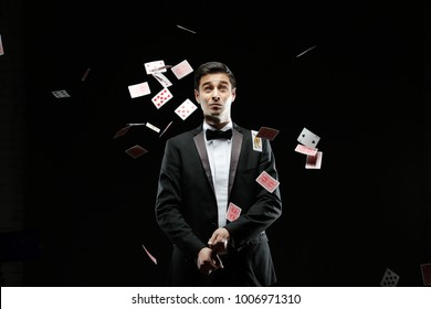 Magician with playing cards,Suprised magician,Juggler man,Mystery person,Black magic,Illusion