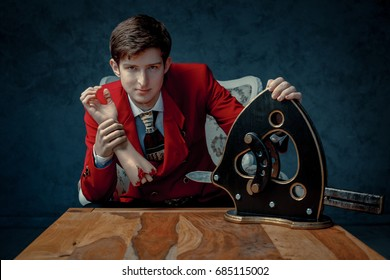 The magician in the red jacket sits at a table with a guillotine and fake severed hand.