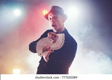Magician showing trick with playing cards. Magic or dexterity, circus, gambling. Prestidigitator in dark room with fog.