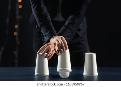 Magician showing tricks with cups on dark background
