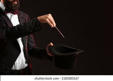 Magician showing tricks on dark background