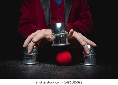 Magician shows shell game of thimbles with circles and ball, black background. Concept deception, sleight hand.