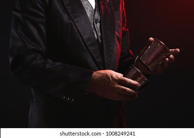 Magician shows trick with a metal cup. Sleight of hand. Manipulation with props.