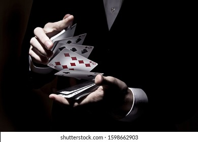 A magician shuffling cards with the spotlight on it