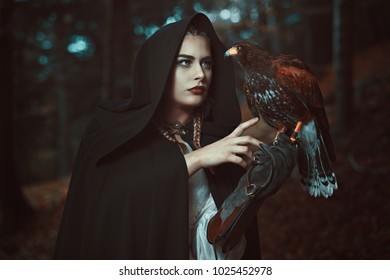 Magician woman with hawk familiar. Forest shot