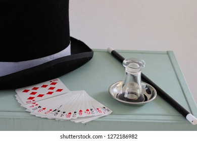 Magician's equipment on a painted chest. Stovepipe hat, cards, glass, coins, magic wand for magic tricks.