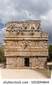 The magician's temple at Mayan ruins Chichen Itza. Impressive Stone building with carved details on every side. The Stone masks on the top floor still show ears, nose and teeth.