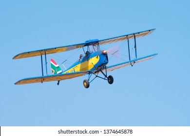 MAGLIESBURG, SOUTH AFRICA-JUNE 23 2018: A yellow and blue Tiger Moth with SA flag flying overhead during the trains, planes and automobile event between Krugersdorp and Magaliesburg