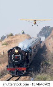 MAGLIESBURG, SOUTH AFRICA-JUNE 23 2018: A yellow Piper Cub flying low over the steam train Susan during the trains, planes and automobile event between Krugersdorp and Magaliesburg