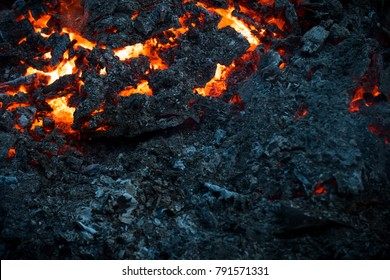Magma textured molten rock surface. Lava flame on black ash background. Volcano, fire, crust. Formation, geology, nature, environment. Danger, hazard, energy concept.