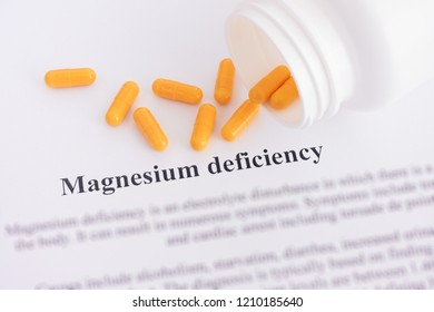 Magnesium deficiency diagnosis on paper with pills spilling out of a bottle. Close up.