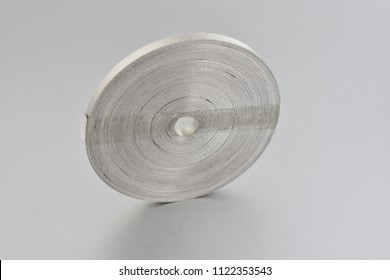 Magnesium ribbon stock images. Laboratory accessories. Laboratory equipment on a silver background. A coil of magnesium ribbon. Chemical element